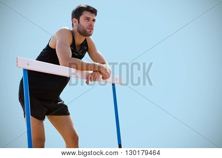 Athletic man pressed on a hurdle posing against blue background
