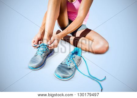 Athletic woman lacing up shoes against blue background