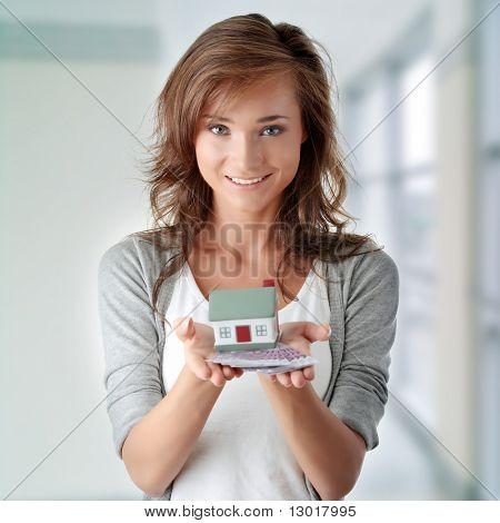 Bella joven sujeta billetes de euros y el modelo de casa sobre blanco - concepto de préstamo inmobiliario