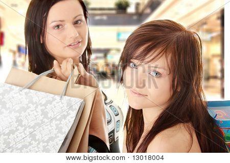 Duas mulheres de compras no shopping mal.