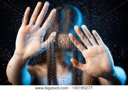 Horror woman behind glass, soft focus. Studio shot