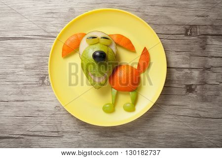 Dog made of juicy fruits on plate