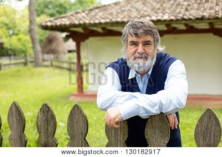 Elderly Man In Front Of His Old House