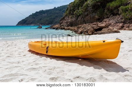 Orange canoe kayak boat lying on a Malaysian beach