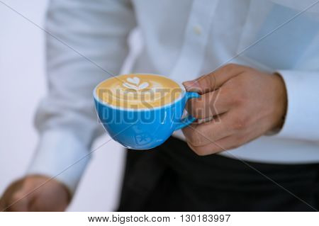 A blue cup of latte art hold by white shirt barista
