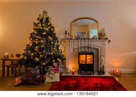 Christmas Tree and Fireplace with a warm glow of Christmas lights and a log burner in festive decoration