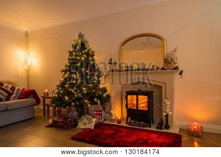 Living Room at Christmas with a warm glow of Christmas lights and a log burner in festive decoration