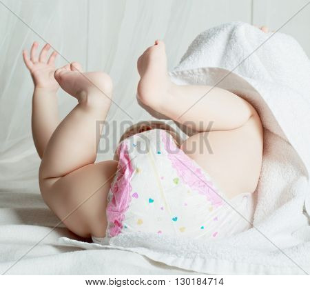 baby wearing diapers in bed at home