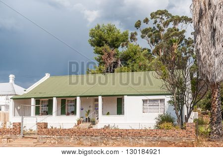 A storm brewing over a typical house in Uniondale a town in the Western Cape Province.
