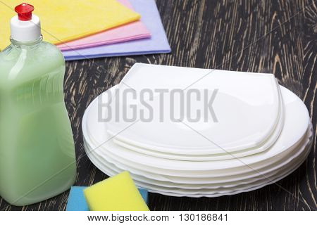 sponges, rsgs, dishes and a bottle of detergent on wooden background