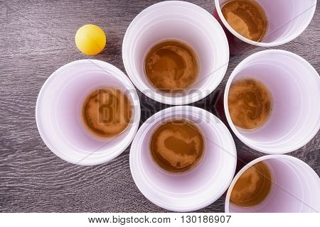 Red plastic cups arranged for playing Beer Pong isolated on wooden background.