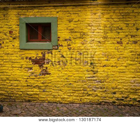Yellow brick wall with a green window