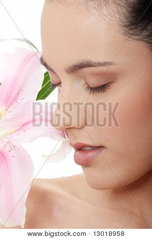 Portrait of the attractive girl without a make-up, with lily flower in hand, isolated on white background