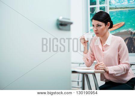 Woman drinking coffee in office kitchen