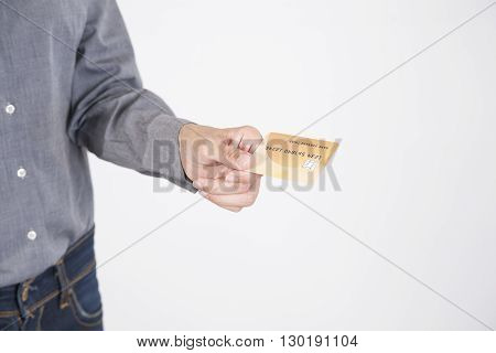 woman blue jeans trousers and grey shirt offering made up fiction credit card in her hands isolated over white background