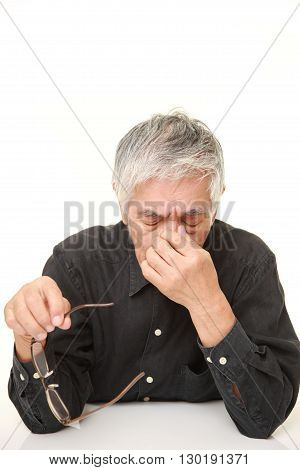 portrait of senior Japanese man suffers from Asthenopia on white background