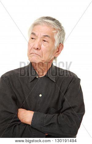 portrait of  senior Japanese man worries about something on white background