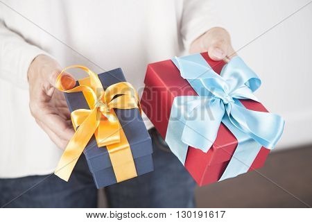 woman blue jeans cream jersey with two gift boxes in both hands blue yellow and red cyan over white background