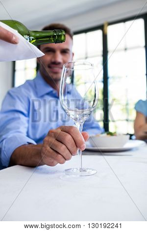 Waiter pouring wine in a glass of costumer sitting at restaurant