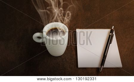 Small cup hot black espresso coffee with blank or empty paper note on wood table with copy space