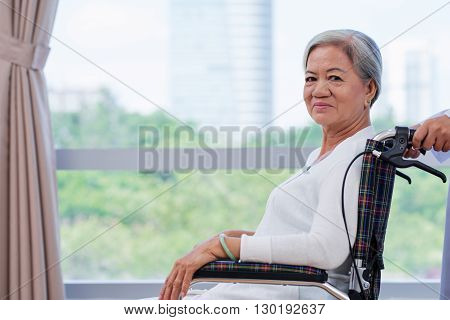 Portrait of smiling senior lungs x-ray Vietnamese woman in wheelchair