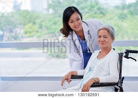 Pretty young doctor caring about elderly woman in wheelchair