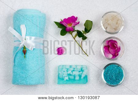 Top view . Close-up. Still life. Bath towel tied with braid with a flower. Handmade soap. Cups with sea salt. All laid out on a white towel.