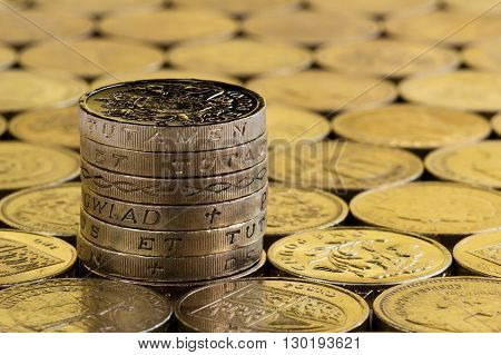 British money pound coins in a neat stack on a background of more money.
