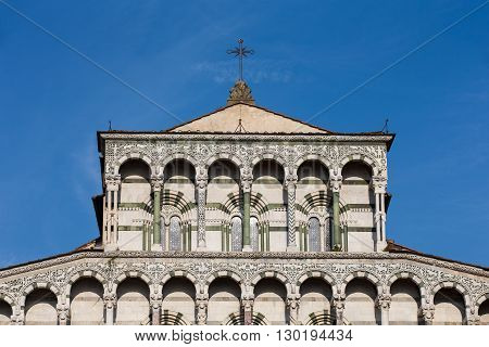 Ornate upper marble facade of the Cathedral of San Martino in the Tuscan village of Lucca Italy showing ornate architectural detail and a cross set against a vibrant blue sky.
