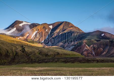 In the hollows of rhyolitic mountain snow. Above the source of hot water steam rises. Early summer morning in the National Park Landmannalaugar, Iceland