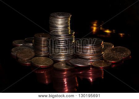 small coins against a dark background with shadows and color patches of light