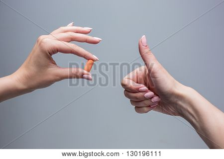 The hands of female doctor holding pill capsule closeup. Medical prescription, pharmacy or insurance concept. Giving or showing medications to patient
