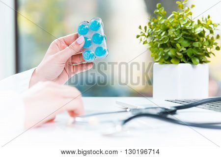 The hand of female medicine doctor holding tablet blister closeup. Medical prescription, pharmacy or insurance concept. Giving or showing medications to patient