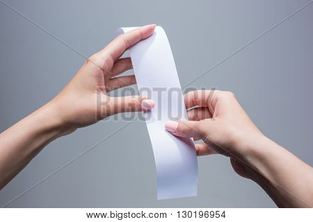 The female hands with  empty transaction paper or paper check on gray background