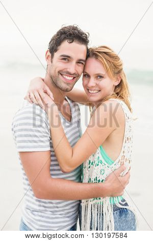 Young couple embracing each other on the beach on a sunny day