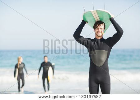 Happy man in wetsuit carrying surfboard over head on the beach