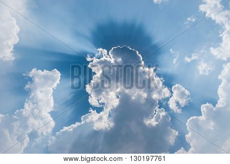 white clouds in blue sky with sunrays