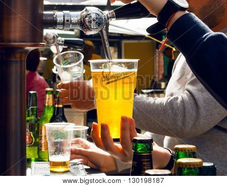 KYIV, UKRAINE - MAY 15, 2016: Bartender pours beer in plastic glass during Street Food Festival on May 15, 2016. Staropramen brewery was founded in Praque in 1869. Second largest brewery in Czech Republic