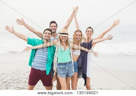 Group of happy friends standing on the beach with their arms outstretched