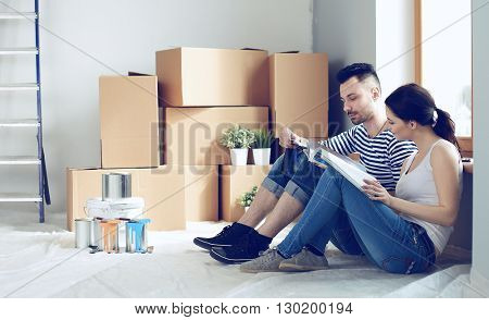 Attractive couple sitting on home floor looking at jurnal and smiling at each other.