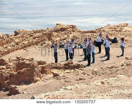 MASSADA ISRAEL - APRIL 23 2015: A group of people raises their arms to the sun at Masada's ruins Israel