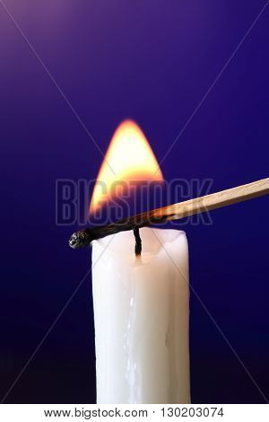 Closeup of candle inflamed with match on dark background