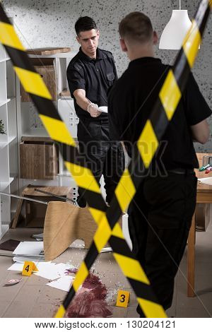 Two policemen during work standing behind yellow crime scene tape