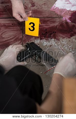 Close up of a policeman holding a gun and an evidence bag