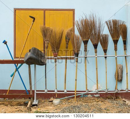 Brooms placed near the wall of the house.