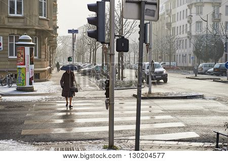 STRASBOURG FRANCE - JAN 20 2016: Silhouette of woman crossing street with umbrella on a snowy day