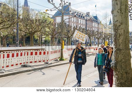 STRASBOURG FRANCE - APR 19 2016: Free City Tour placard in guide hand explaining to tourists about the history of the old city of Strasbourg Alsace France