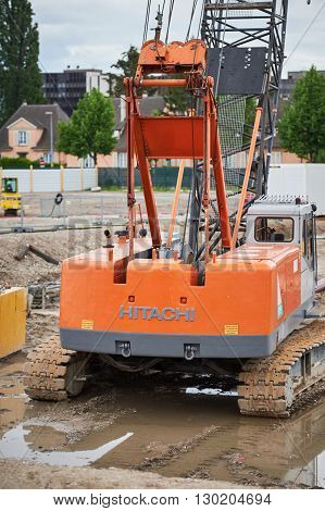 STRASBOURG FRANCE - MAY 15 2016: HITACHI excavator in a puddle on a construction site waiting to perate