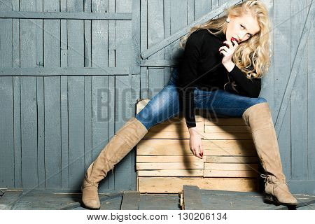 Pretty blonde in jeans and boots with long curly hair and red lips sitting and posing near wooden wall