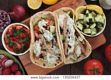 Turkish doner kebab, wrapped sandwich with meat slices and fresh vegetables